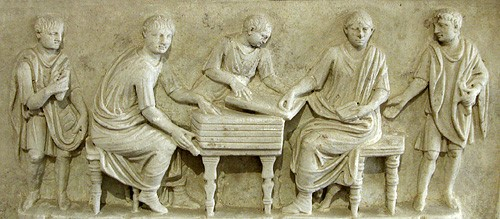 This beautifully carved altar was set up for Q. Fulvius Faustus and his brother Quintus Fulvius Priscus, who served as scribae librarii (public secretaries or clerks) of the curule aediles. The upper relief shows the brothers at work handling tablets, while the lower relief shows citizens, some holding scrolls or small tablets, gesturing toward the inscription in admiration (note the presence of women and children). Rome, Terme Diocleziano (National Museums). Credits: Barbara McManus, 2004